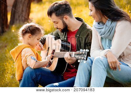 Young Man Playing Guitar With Family