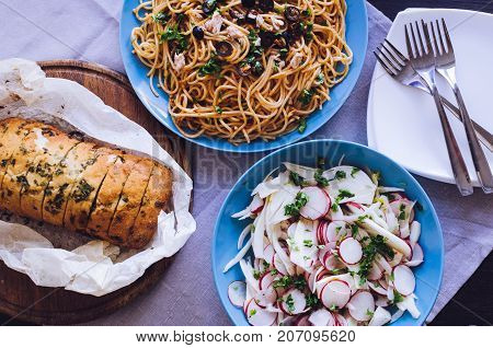 Traditional Italian dinner - Spaghetti Alla Puttanesca pasta with black olives tuna anchovies capers and parsley vegetable salad and baked ciabatta. Vegetarian food. Italian cuisine. Top view.