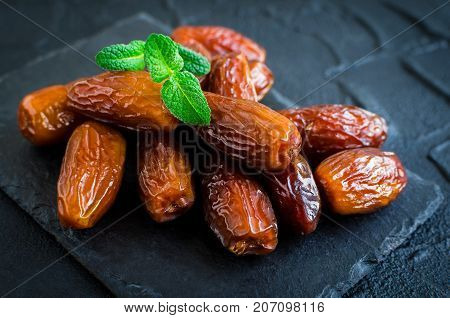 Dried date and green mint on black stone background. Heap of dates close up. Healthy snack.