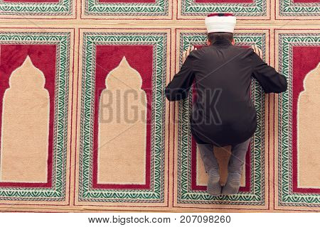 Top view of a religious muslim man praying inside the mosque.