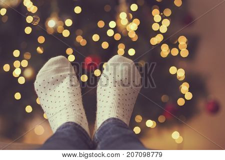 Detail of woman's feet wearing warm winter socks placed on the table with nicely decorated Christmas tree and Christmas lights in the background. Selective focus