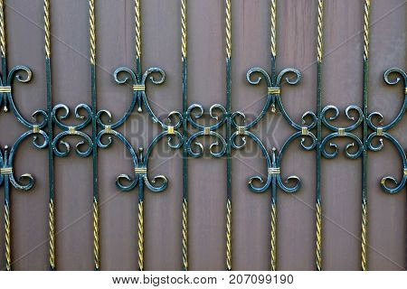 fragment of a fence with forged bars and a beautiful pattern