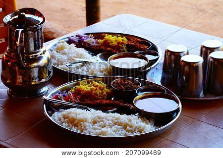 Traditional Indian food - thali. Meals with many ingredients: sauces, rice, fish, curd and salad. Jug of water and glasses on the table.