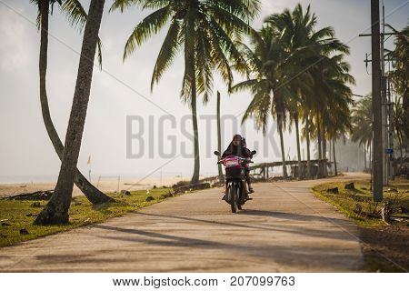 Khok Khian Thailand - January 7 2014: A southern muslim housewife rides her kid to school in peaceful morning of Banthon beach Narathiwat Thailand.