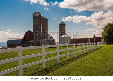 Four silos several barns and tractors on green grass with a blue sky background