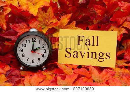 Fall Savings message Some fall leaves and retro alarm clock and yellow card with text Fall Savings