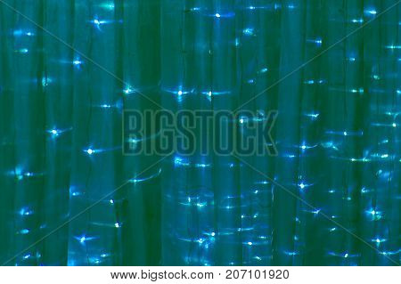 Christmas drape with lights of green color. The background is a Festive fabric.