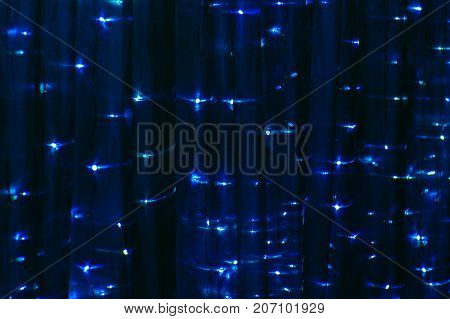 Christmas drape with lights of blue color. The background is a Festive fabric.