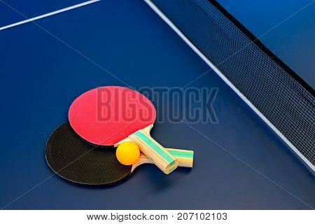 Table tennis table with rackets net and orange ball