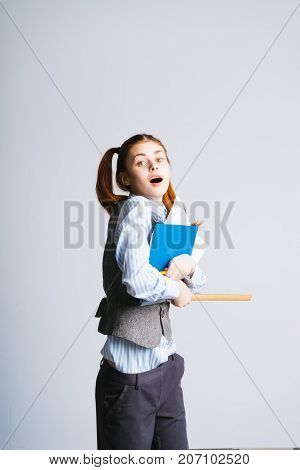 funny girl with two tails holds in her hands folders and ruler