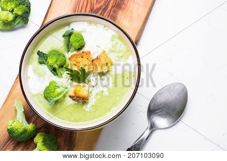 Green soup puree or cream soup with broccoli and croutons on white table. Top view copy space.