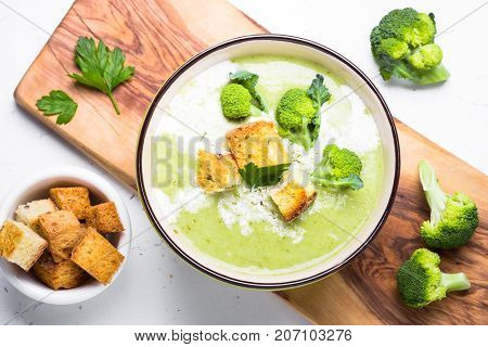 Green soup puree or cream soup with broccoli and croutons on white table. Top view.