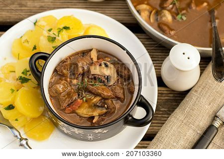 Beef stew goulash with bacon and mushrooms served with potatoes