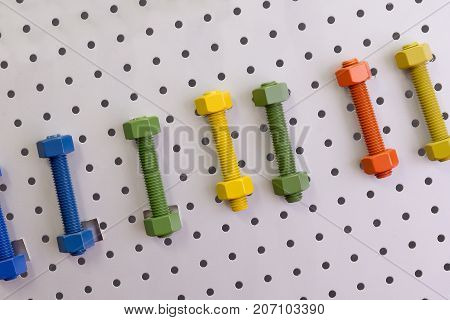 The multi-color of screw bolt and nut attach at the board.the industrial tool