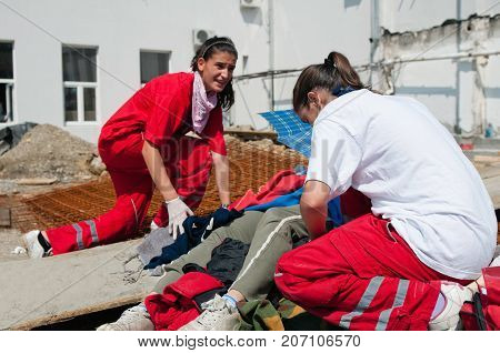 Female Paramedic Helping A Construction Worker, Color Image, Selective Focus, Outdoors
