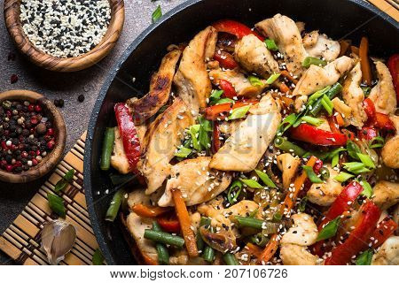 Chicken stir fry with vegetables soy sause and sesame in the wok. Traditional chinese food. Top view Close up.