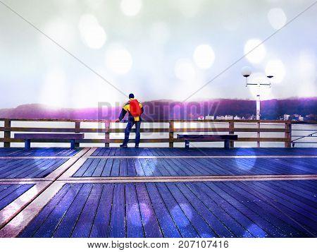 Man Tourist In Autumn Mist On Wooden Pier Above Sea. Depression, Dark  Atmosphere. Touristic Mole