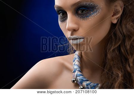 The portrait of a young and beatiful girl with the artistic make-up on the dark blue background . She has perfect skin tone and curly hair. There is an intresting blue and white bijou on her neck.
