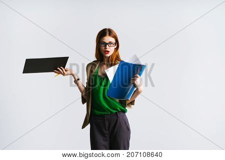 red-haired lady in glasses is standing with documents in hands and looking at camera