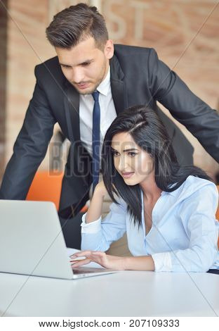business couple in an office working on the computer.