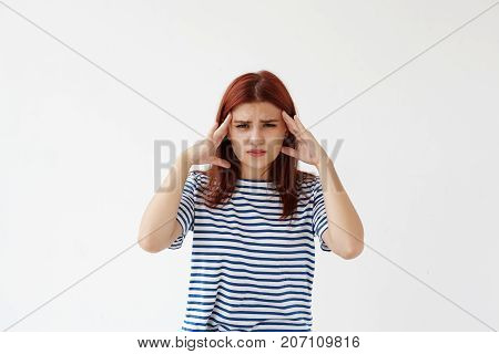 Student girl in sailor shirt frowning looking at camera with painful expression and squeezing temples having headache or migraine becuase of stress she experiencing during preparations to exams
