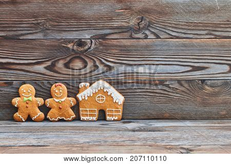 Christmas homemade gingerbread cookies on wooden background. Gingerbread house and couple - man and woman.