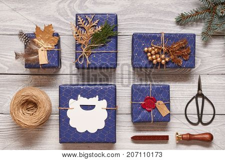 Creatively wrapped and decorated christmas presents in boxes on white wooden background.Top view from above. Flat lay.
