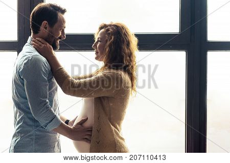 Expressing feelings. Beloved pleasant couple looking at each other and hugging while expressing delight and love