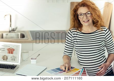 Finally chosen. Smiling attractive woman standing at the table and touching her belly while pointing at the color on papers and looking at you with joy