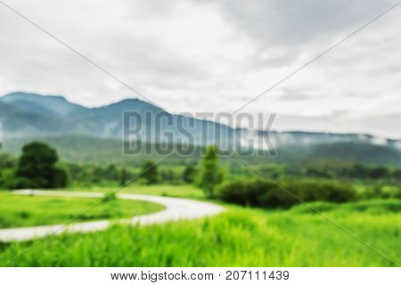Blurry grass nature field with car road way in weather rainy cloudy day vintage picture style countryside of Thailand.