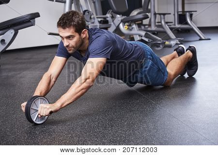 Guy performing ab wheel exercise in gym