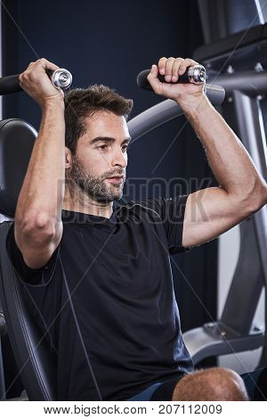 Strength training guy performing shoulder press in gym