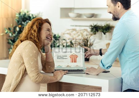 Listening carefully. Positive pregnant woman standing at the table and putting the hand under the chin while listening to her husband