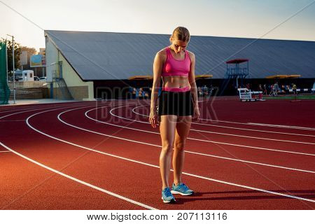 Picture of beautiful young European female runner or sprinter standing on outdoor stadium track, feeling exhausted after sprint or marathon. Jogging, sport, healthy active lifestyle concept.
