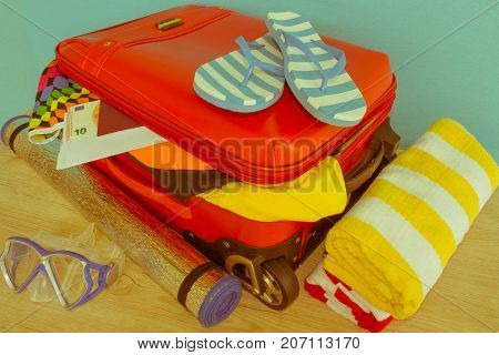 Suitcase with things for spending summer vacation. Anticipation of voyage. Women's clothes and accessories in red suitcase - Retro color
