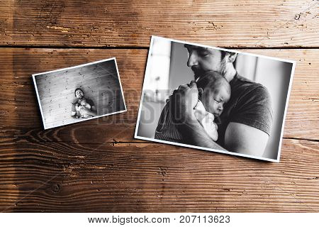 Pictures of young father and his cute newborn baby daughter laid on table. Fathers day concept. Studio shot on wooden background.