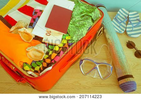 Open red suitcase packed for travelling close up. Suitcase with different things prepared for travel - Retro color