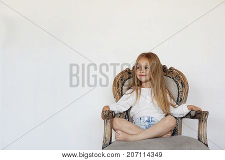 Isolated shot of charming positive 7-year old Caucasian girl sitting cross legged on fancy luxurious armchair and smiling dressed in white blouse and denim shorts. Playful child having fun indoors