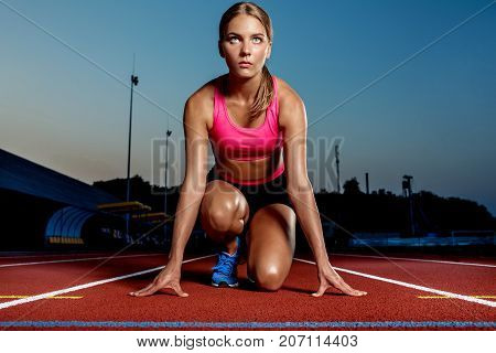 Portrait of beautiful woman ready to start running. Female athlete sprinter doing a fast sprint for competition on red lane at an outdoor field stadium.