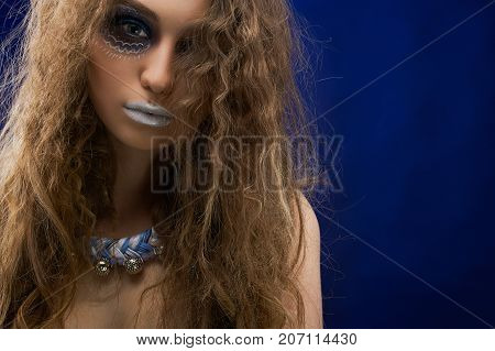 A picture of mysterious girl with long curly hair, green eyes and pefect skin. She has intresting make up with patterns on her face. A girl wears a blue and white bijou.