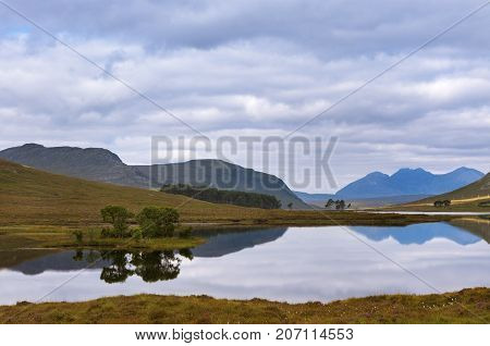 Beautiful lake with reflections of the trees and surrounding mountains in the Scottish Highlands, in Scotland, United Kingdom; Concept for travel in Scotland