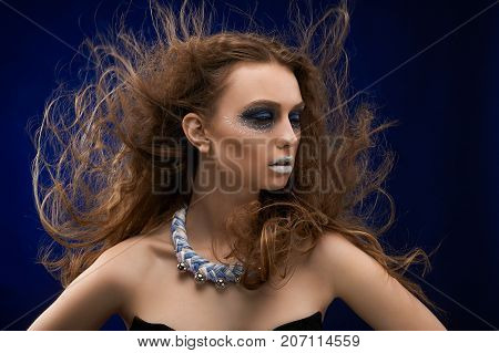 A portrait was done on the dark blue background in the studio. Pretty girl on the photo has beatiful, original make-up , perfect skin color and long, curly hair.There is a bijou on her neck.