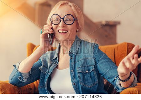 Glad to hear you. Cheerful smiling aged woman talking on phone and sitting at home while enjoying a pleasant conversation