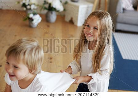 Pretty European girl dragging her baby brother by t-shirt and laughing while doing conga line. Children enjoying indoor games on rainy autumn day. Childhood fun joy relaxation and entertainment