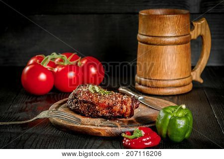 Grilled steak seasoned with spices and fresh herbs served on a wooden board with wooden mug of beer, fresh tomato, red and green peppers. Black wooden background. Still life