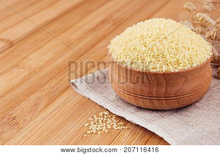 Couscous in wooden bowl on brown bamboo board closeup. Rustic style healthy dietary groats background.