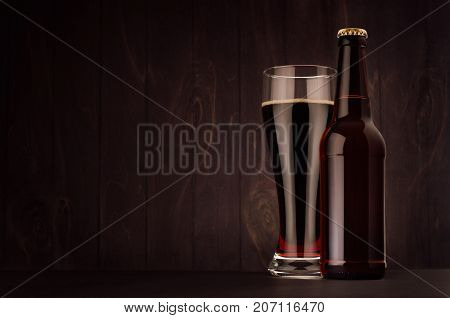 Brown beer longneck bottle and glass weizen with porter on dark wood board copy space mock up. Template for advertising design branding identity.