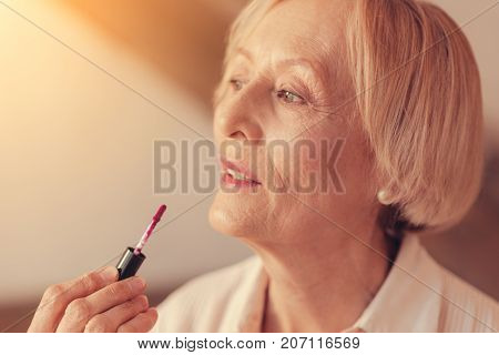 Sat yes to your beauty. Close up of a senior nice woman looking aside and using her lip gloss while doing a make up
