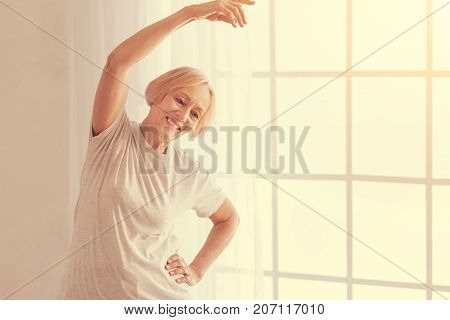 Do it with pleasure. Joyful smiling aged woman enjoying morning exercises while going in for sport at home