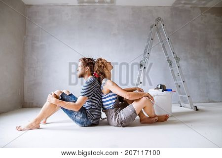 Beautiful young couple painting walls in their new house, sitting on the floor, dreaming. Home makeover and renovation concept.
